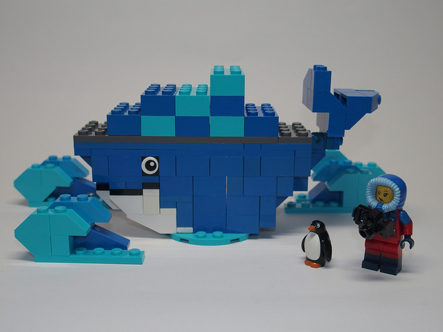 A Lego Docker logo, with a penguin figurine next to a Lego man in a parka.